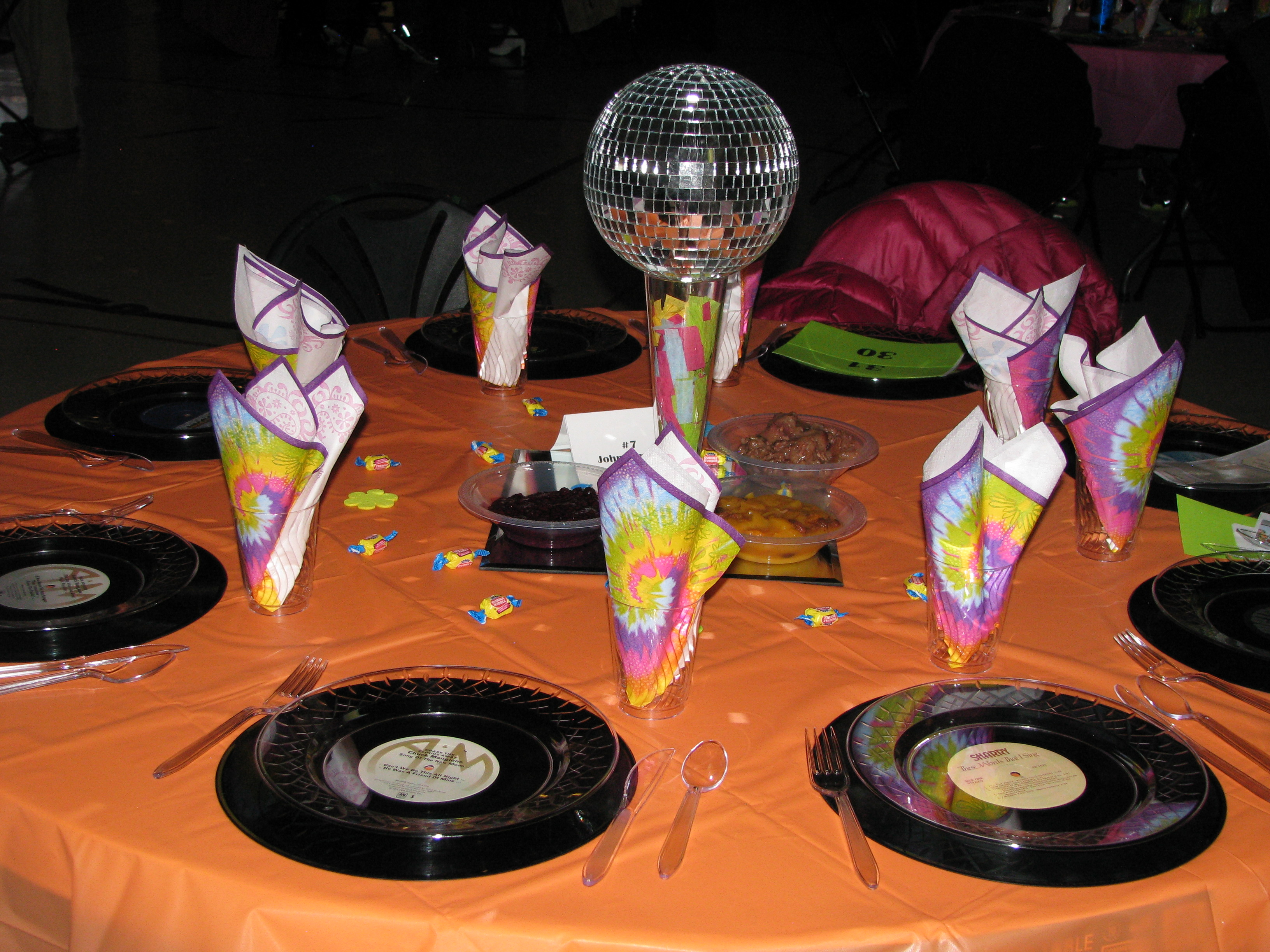 Disco ball centerpieces and tie dye napkins for 70s decoration