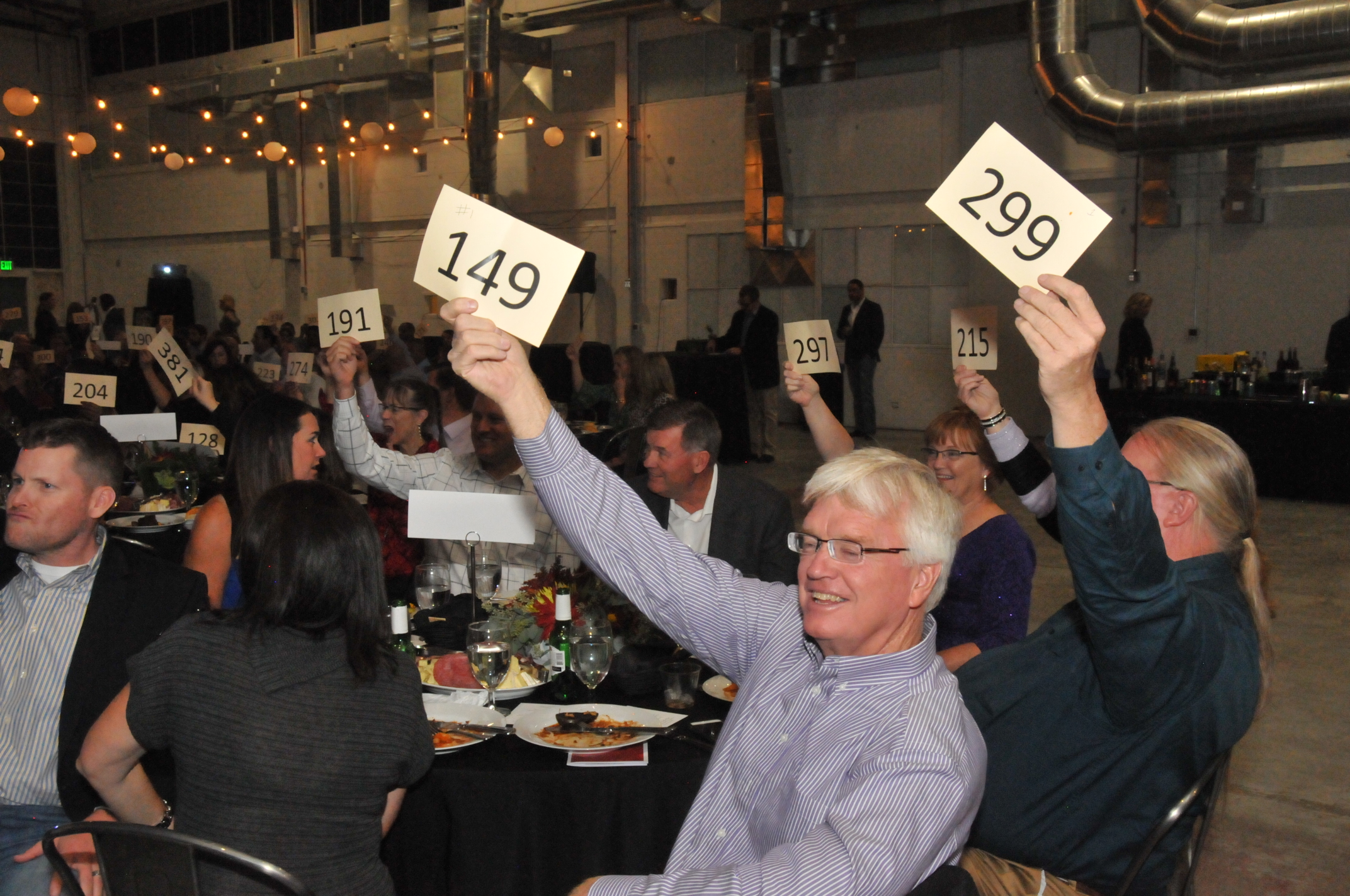 Guests enthusiastically bid on various live auction items for How to bid at a live auction